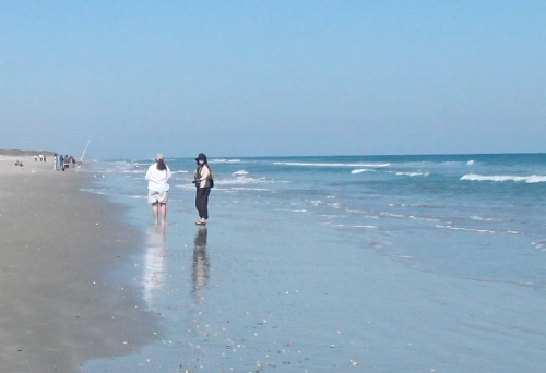 Donna and Dawn walk on the beach.